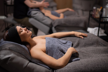 good-looking women came in spa welbbeing salon to get anti aging lifting massage, lie on desk and enjoy calmness, have rest
