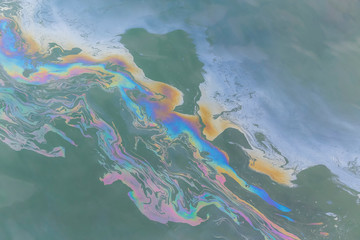 trail of oil on water in ocean creating a colourful trail