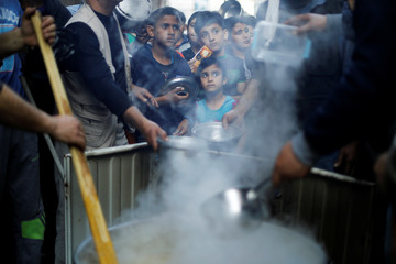 Palestinians gather to get soup offered for free during the Muslim fasting month of Ramadan in Gaza City