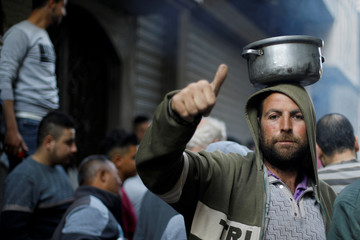 Palestinian gestures as he waits to get soup offered for free during the Muslim fasting month of Ramadan in Gaza City