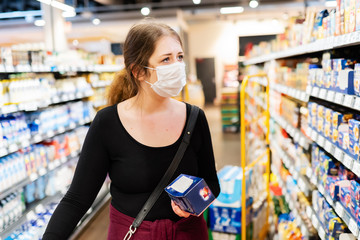 young woman with filtering facepiece in a supermarket
