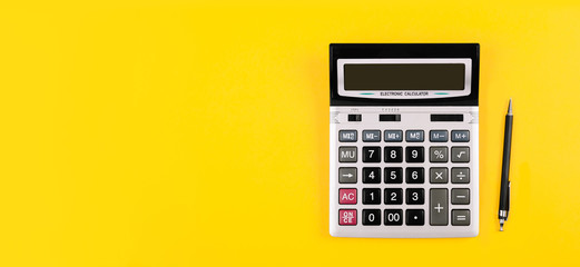 Large silver calculator with gray and black buttons and black pen on a yellow background. Conceptual photo of calculations, accounting, computing, profit, loss, tax.