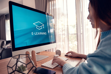 Online education, e-learning. Young woman is sitting at table, working on computer monitor with inscription on screen e-learning and image of square academic cap, distance training.