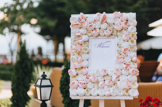Wedding, festive stand, decorated with fresh roses, with invitational words welcome stands at the ceremony against the backdrop of nature. Photography, concept, copy space.