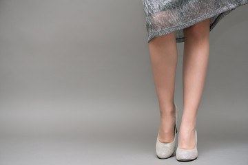 Female legs in pantyhose in high heel shoes close up on gray background.