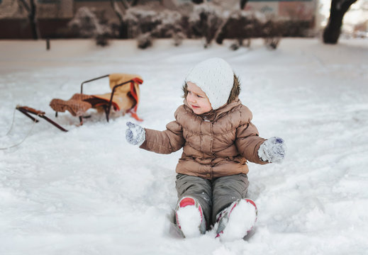 Little funny girl in a brown down jacket, gray pants and a white hat sits in the snow and cries. The concept of bad mood due to unsuccessful sledding.