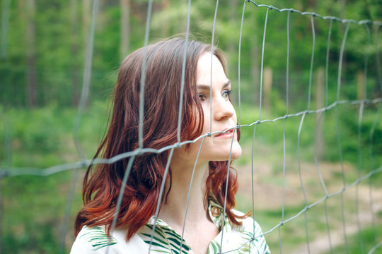 Beautiful redhead girl behind fence outdoors. Psychological concept of limiting beliefs, phobias or fears