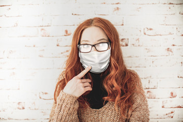 Young, attractive, red-haired woman with curly hair and foggy glasses wears a breathing mask in the pandemic