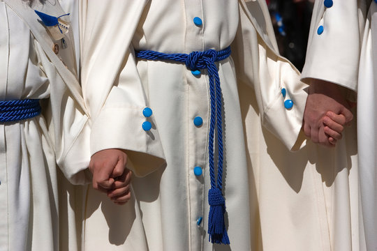 penitents with white tunics gathers of the hand during a procession of Holy Week, Spain