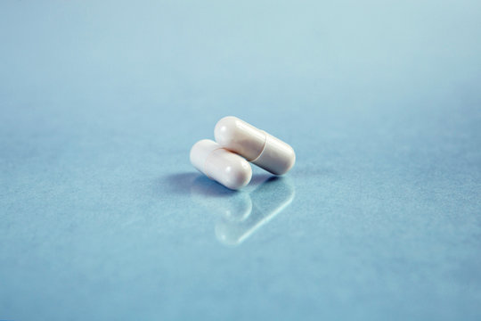 Two white capsules on blue background. Dose of prescription pills.