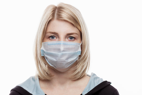 A close-up of an adult white woman wearing and adjusting a disposable mask on her face. On a white background. Available space for text.