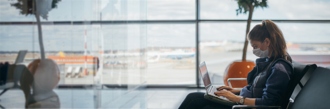 A woman is sitting at the airport with a laptop in a medical mask