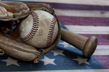 Closeup view of a vintage baseball equipment on rustic wooden United States Flag
