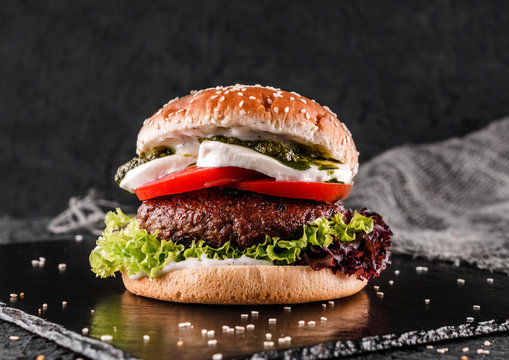 Tasty burger with mozzarella cheese, tomatoes, lettuce and sauce pesto on slate black background, close up