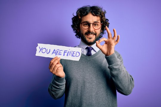 Handsome business man with beard holding you are fired message over purple background doing ok sign with fingers, excellent symbol