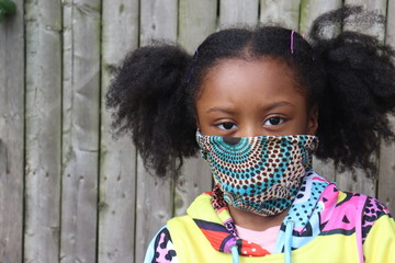 Girl Wearing Cloth Face Mask outside wooden fence background