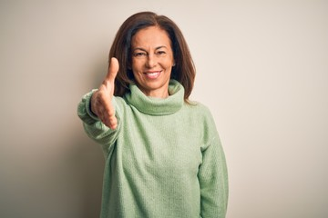 Wall Mural - Middle age beautiful woman wearing casual turtleneck sweater over isolated white background smiling friendly offering handshake as greeting and welcoming. Successful business.