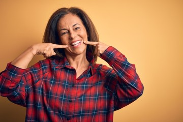 Wall Mural - Middle age beautiful woman wearing casual shirt standing over isolated yellow background smiling cheerful showing and pointing with fingers teeth and mouth. Dental health concept.
