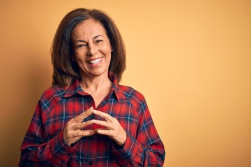 Wall Mural - Middle age beautiful woman wearing casual shirt standing over isolated yellow background Hands together and fingers crossed smiling relaxed and cheerful. Success and optimistic