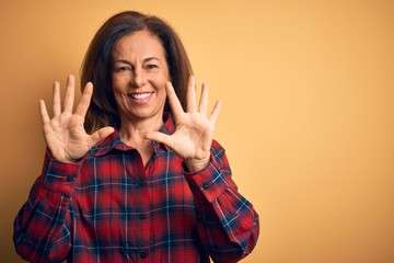 Wall Mural - Middle age beautiful woman wearing casual shirt standing over isolated yellow background showing and pointing up with fingers number ten while smiling confident and happy.
