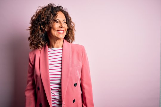 Middle age beautiful businesswoman wearing elegant jacket over isolated pink background looking away to side with smile on face, natural expression. Laughing confident.