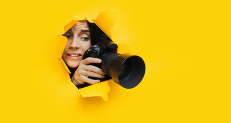 A young paparazzi girl holds a reflex camera and looks through a torn hole in yellow paper. The concept of embarrassment, shame for what he saw. Copy space.