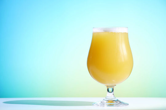 A hazy New England India pale ale beer in a tulip shaped glass against a blue background.