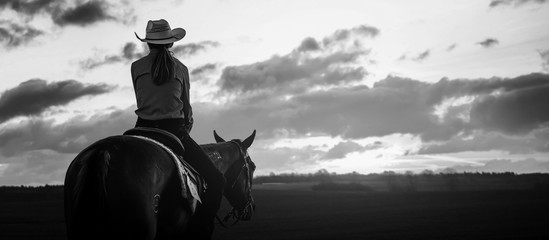Girl ride on a horse in farm open field at afternoon dark sunset time.black and white  Papier Peint