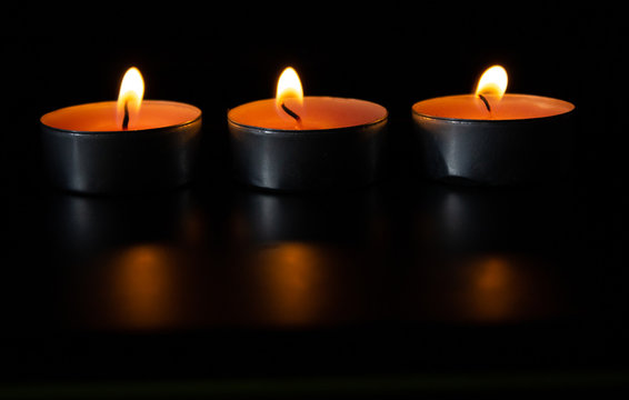 Composition of three candles on dark luxury night background. Black table, side view. Candles Burning at Night. Orange taper burning in focus, foreground. illustration design.