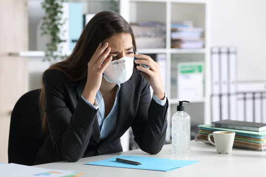 Worried executive with mask calling on phone at office