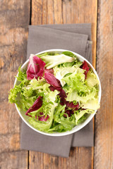 Wall Mural - bowl of lettuce on wood background