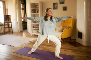 Full length shot of happy energetic mature woman in casual clothes exercising at home because of social distancing, practicing yoga on mat, standing in warrior ii pose. Age, wellness and health Wall mural