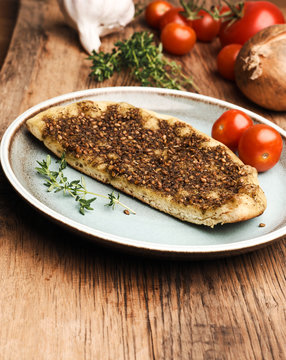 Tasty manaqish with thyme and sesame on a rustic plate with different ingredients