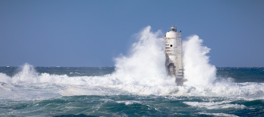The lighthouse of the boat-eater shrouded by the waves of a mistral wind storm