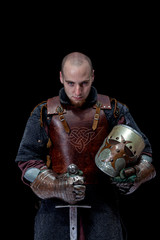 Knight with helmet and sword isolated on black background