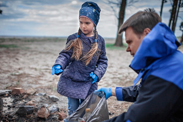 Kids with their father cleaning area in forest near beach, save the planet concept