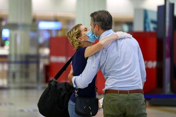 A man kisses his wife before she boards at Dubai International Airport, as Emirates airline resumed limited outbound passenger flights amid the outbreak of the coronavirus disease (COVID-19) in Dubai