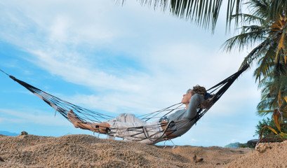 Papiers peints Pont Relaxed woman swinging in a hammock at sand beach of Thailand