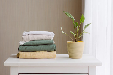 a neat stack of folded women's clothing in natural colors on a white wooden chest of drawers, a...