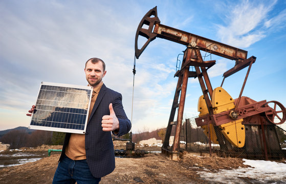 Businessman holding portable solar panel, showing approval gesture, standing on territory of oil field with pump jack and sky on background. Concept of petroleum industry and alternative energy.