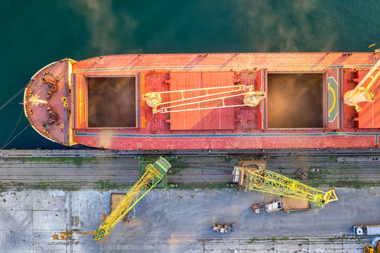 Top view from drone of a large ship loading grain for export. Water transport