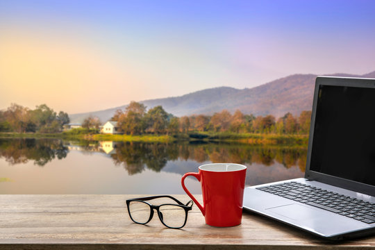Laptop with red coffee cup and eye glasses on wooden table on blurred beautiful landscape in morning  background. work from home concept.