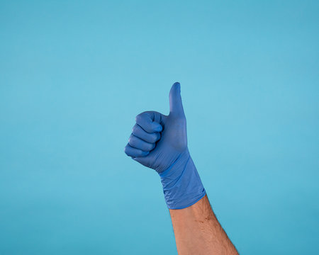 Male Hand in blue surgical latex gloves making thumbs up gesture isolated on blue background