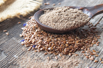 Crushed flax seed in a wooden spoon on a pile of flaxseed.