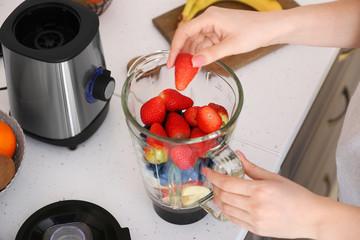 Fotobehang - Woman making healthy smoothie at home, closeup