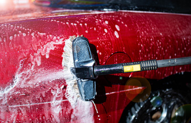 Hand washing with brush and compressor of a red car.