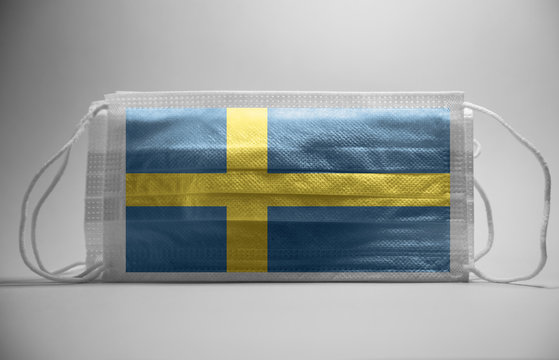 Coronavirus in Sweden Concept.Dramatic atmosphere Sweden Flag printed on surgical protective mask.Corona virus restrictions in Sweeden
