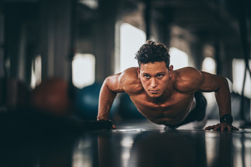 Muscular and strong athletic man doing Push up exercising in sport gym.