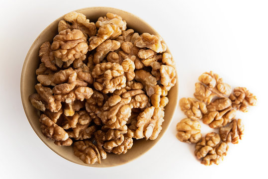 Walnut dry fruits in a brown bowl against a white background