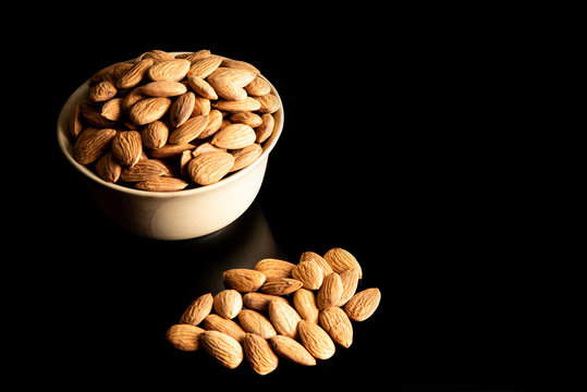 Almond Dry fruits in a brown bowl against white background